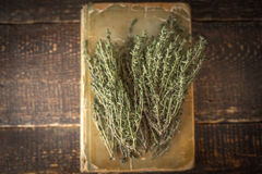 Old recipe  book with thyme on the wooden table top view Royalty Free Stock Photo