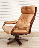 Old recliner. Old worn and dirty brown leather recliner chair Royalty Free Stock Photo
