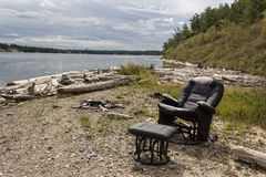 Old recliner by the lake. Old black recliner with foot stool by the lake in summer Stock Photo