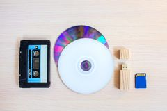 Old recorder cartridge, USB stick, and compact disks in a row royalty free stock photo