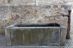 Old rectangle well with running water from fountain tap in Glurn. Old rectangle well with running water from fountain tap at commune named Glurns Glorenza, in Stock Photography