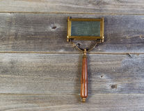 Old rectangular shaped magnifying glass on rustic wood Royalty Free Stock Images