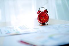 Old red alarm clock, red alarm clock Placed in the workspace. White room Beautiful colors. stock photo