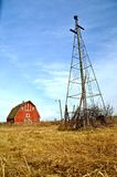 Old red barn dwarfed by a wind mill Royalty Free Stock Image
