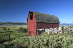 Old red barn in Montana. An old red traditional stands at the side of ranchlands in Big Sky Country, Montana Royalty Free Stock Photo