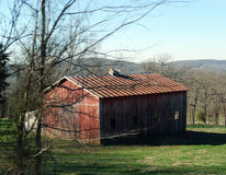 Old red barn in the ozark mountains. Red barn with vertical siding and a metal roof in the rural ozark mountains near Devil`s Den State Park. Vertical siding Royalty Free Stock Photos