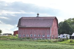 Old red barn. An old red barn showing a few small sheds and a trailer to one side Royalty Free Stock Photography