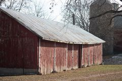 Old red barn with silo on a farm in late autumn on a sunny day royalty free stock photos