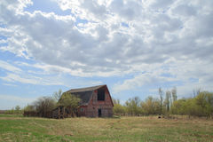 Old red barn under cloudy sky Stock Images
