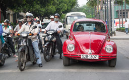 Old Red Beatle standing at the cross road. Traffic in Saigon (Ho Chi Minh), Vietnam Royalty Free Stock Photo