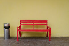 Old red bench on dirty floor and yellow wall Stock Image