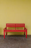 Old red bench and  dirty yellow wall Stock Images