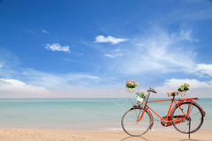 Old red Bicycle with basket  flowers on beautiful beach tropical Royalty Free Stock Photography