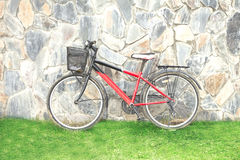 Old red bicycle leaning against a wall Royalty Free Stock Photo