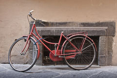 Old red bike. An old red bike laid on a wall Stock Photo