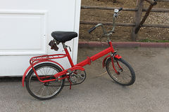 Old bike. Old red bike in front of white door Stock Photos