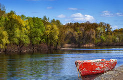 Old red boat. Red old boat anchored by the river bank over stunning autumnal river scape Stock Photo
