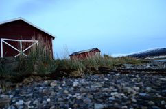 Old red boat house next to sea shore Royalty Free Stock Photo