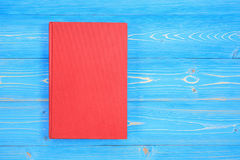 Old red book on wooden plank background. Blank empty cover for d. Top view old red book on wooden plank background. Blank empty cover for design Stock Photography