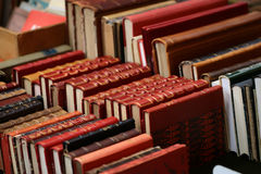 Old red books. Rows old used red vintage hardcover books leaning against each other, horizontal photo Stock Photos