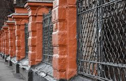 Old red brick and black lattice fence stock images