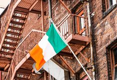 Irish Flag on Old Red Brick Buildings. An old red brick building with metal fire escape flying an Irish flag royalty free stock images
