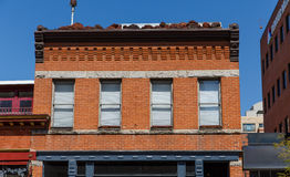 Old Red Brick Building with Shaded Windows Stock Images
