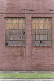 Old red brick building showing signs of abandonment with two busted windows. Stock Photography