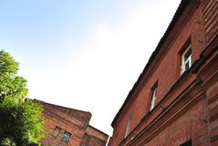 Old red brick building walls with windows, green trees, view from ground on slate roof, blue sky. Background stock image