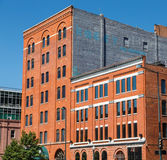Old Red Brick Buildings with Blue Windows Under Clear Sky Stock Image