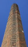 Old red brick chimney (low angle shot) with ladder Stock Image