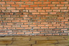 Old red brick and concrete wall with bamboo floor stock images