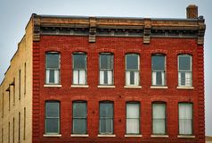 Old Red Brick Historic Down Town Apartment Building. This picture is of an old antique looking red and beige brick apartment building located just outside of the stock photography