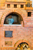 Old red brick oven and a pot Stock Image
