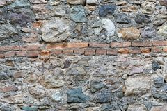 Very ancient wall with stones and bricks. Old red brick and stone wall background texture with some grass in high resolution details. Very ancient wall with royalty free stock photos