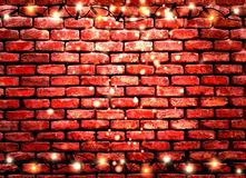 Old red brick wall background with garland and sparks Stock Photo