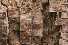 Old red brick wall background. Vintage destroyed brown brick wall. Texture of ruined brick wall, cement background. Old red brick wall background. Vintage royalty free stock photo