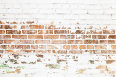 Old red brick wall with damaged white paint layer. Closeup background photo texture Stock Photo