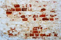 An old red brick wall with fallen off white plaster. royalty free stock photography