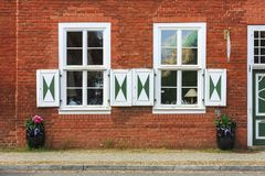 Old style windows in red brick wall in Potsdam, Germany. Old red brick wall featuring large old style windows with wooden shutters in Potsdam, Germany Stock Images