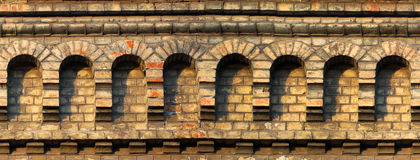 Old red brick wall fragment with arches. Horizontal seamless arc Stock Photos