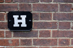 Old red brick wall with H Hydrant sign Stock Photo