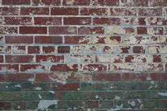 Closeup surface pattern of an old brick wall with green grey and yellow paint textured background stock photo
