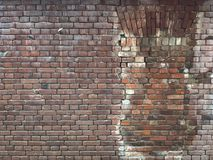Old red brick wall with a window pane, restored by stones of the same type royalty free stock photo