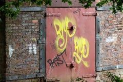 Old red bricks and metallic door. Old red bricks and a metallic door reflect industrial style stock image