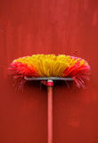 Old red broom with metal hand grip against red wall. Royalty Free Stock Images