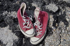 Old Red Canvas Shoes - Asphalt Background Royalty Free Stock Photos