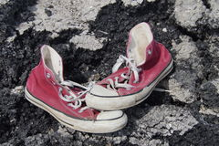 Old Red Canvas Shoes - Asphalt Background Stock Images