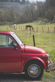 Old red car and a tuscan landscape Royalty Free Stock Image