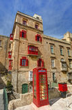An old red cardphone booth in the historic city Valletta with an old appartment building in the background Stock Photography